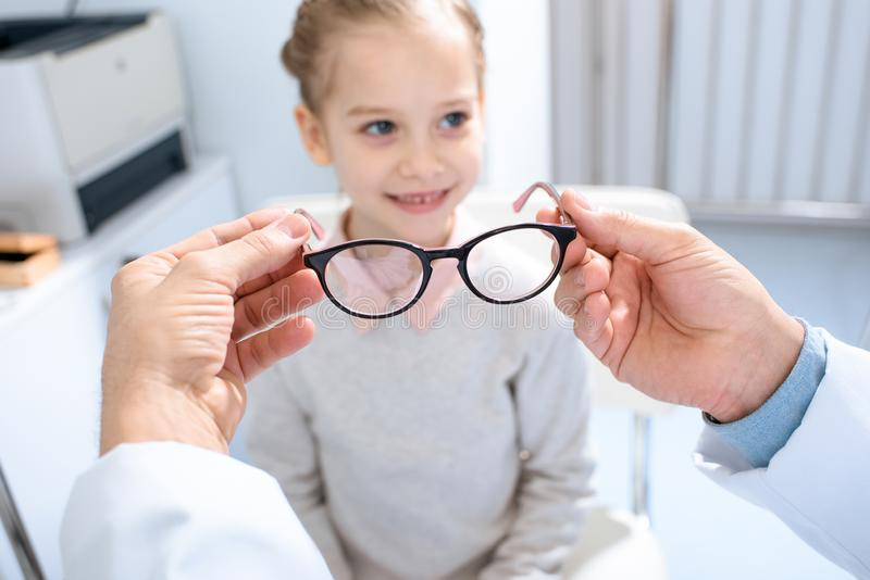Cropped image of ophthalmologist proposing new glasses to pre-adolescent child. In clinic royalty free stock image