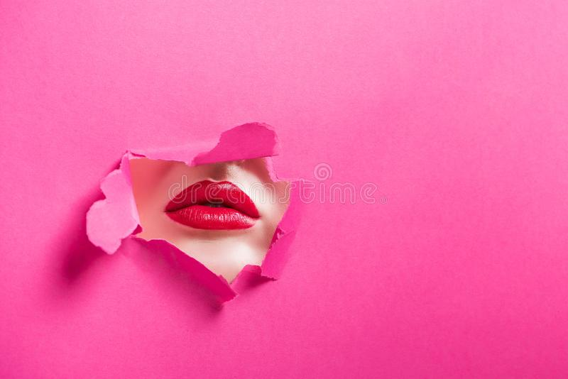 cropped image of passionate girl showing lips in hole stock image
