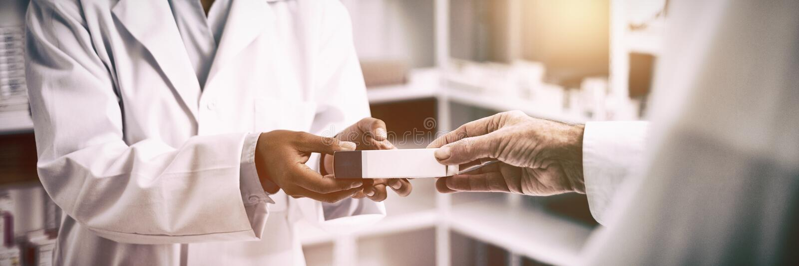 Cropped image of patient hand taking box from pharmacist stock photography
