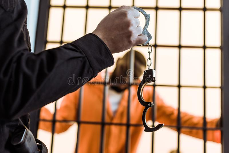 Cropped image of prison guard showing handcuffs to african. American prisoner royalty free stock photos
