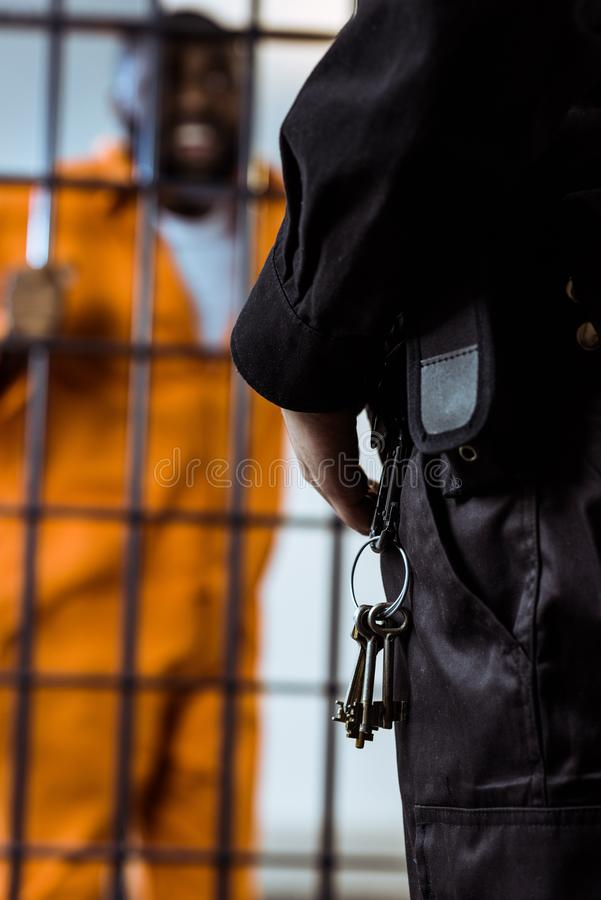 cropped image of prison guard standing near prison bars stock images