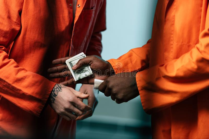 Cropped image of prisoner buying drugs at african. American inmate royalty free stock image
