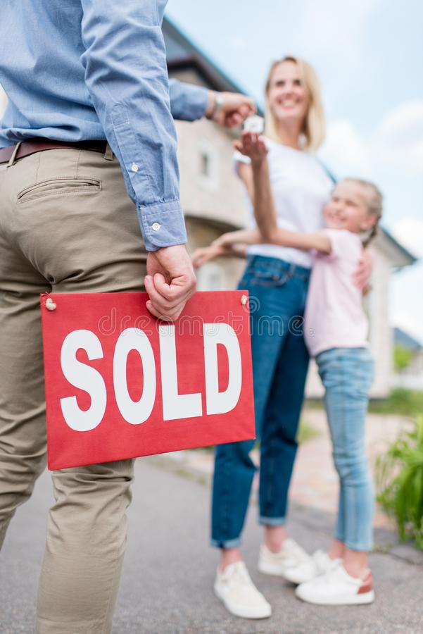 Cropped image of realtor with sold sign giving key to young woman. With daughter in front of new house stock photography