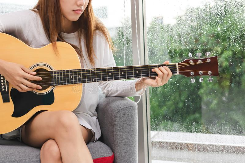 Cropped image of relaxed young Asian woman playing acoustic guitar in living room royalty free stock photos