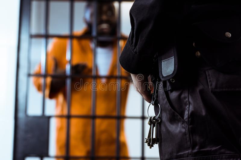 cropped image of security guard standing near prison bars royalty free stock photo