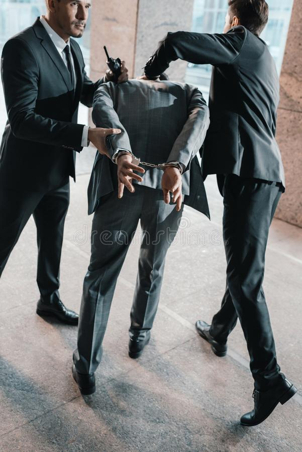 Cropped image of security guards. Arresting offender stock images