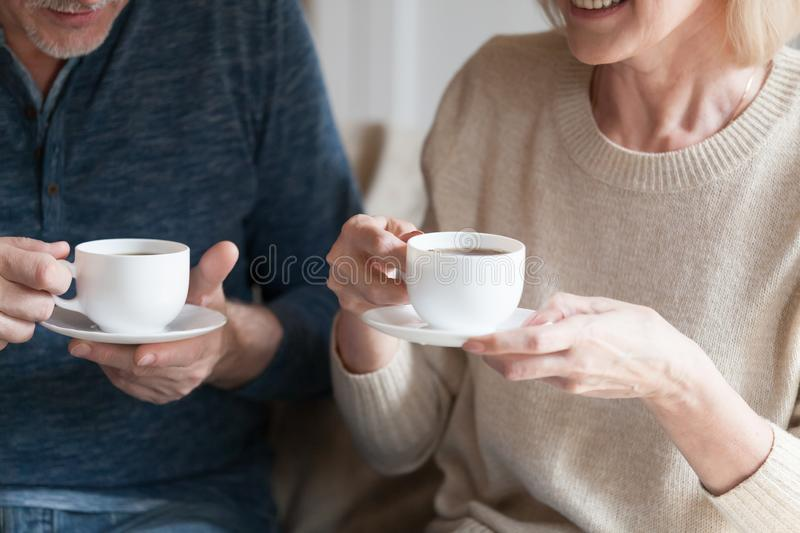 Cropped image senior spouses holding cups with tea stock photo