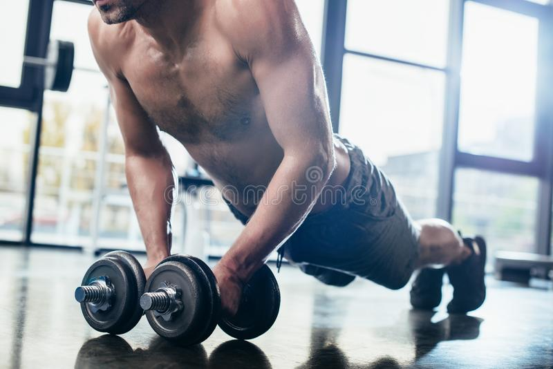 Cropped image of shirtless sportsman doing plank on dumbbells. In gym royalty free stock photos