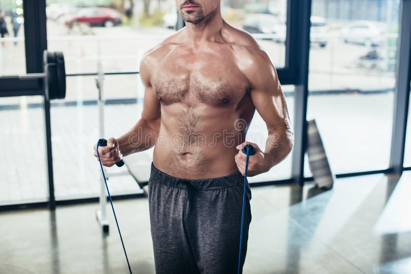 Cropped image of shirtless sportsman training with jumping rope. In gym stock photos