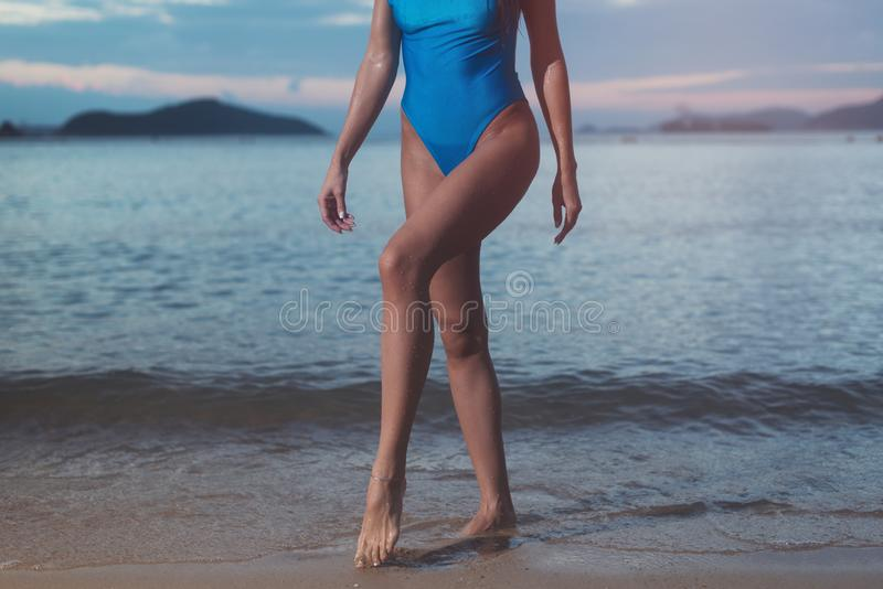 Cropped image of slim young woman wearing trendy blue swimsuit walking in the sea at sunset royalty free stock images