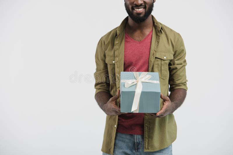 Cropped image of smiling african american man holding present box. Isolated on white stock photography