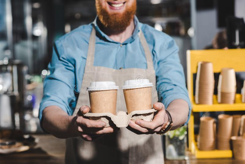 Cropped image of smiling male barista holding two disposable cups of. Coffee royalty free stock image