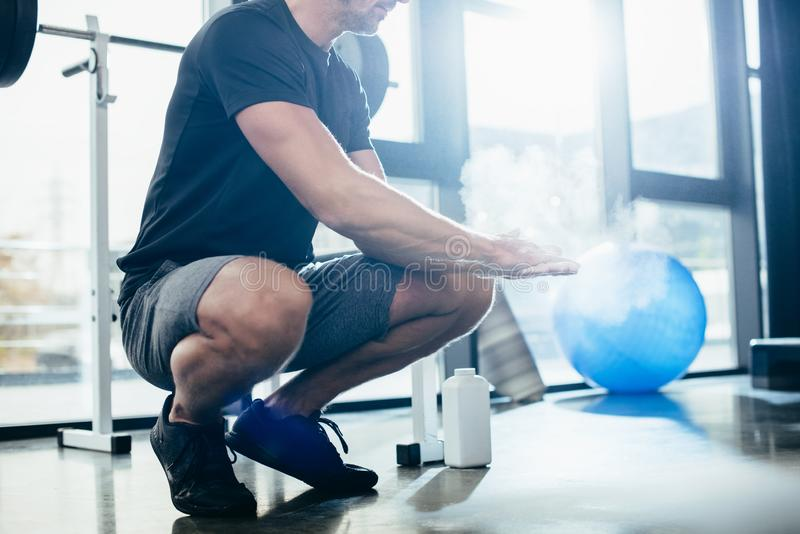 Cropped image of sportsman applying talcum powder on hands exercising training. In gym stock photos