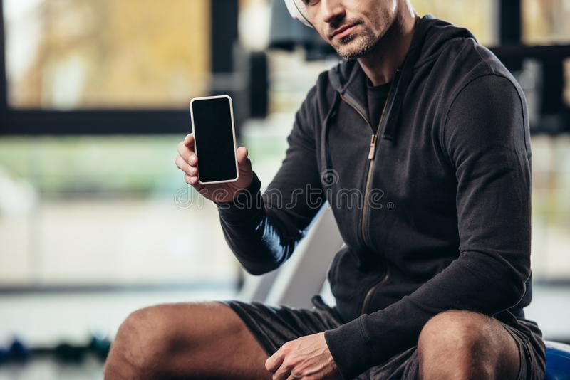 Cropped image of sportsman showing smartphone with blank screen. In gym royalty free stock photo