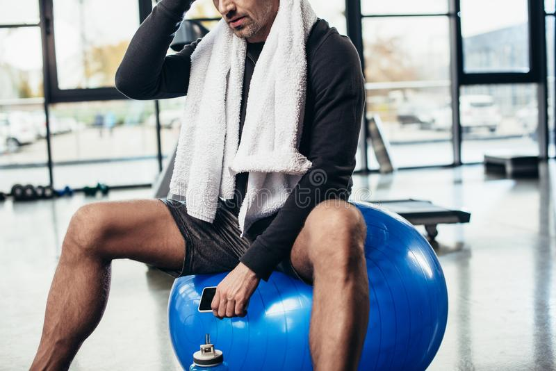Cropped image of sportsman sitting on fitness ball with towel and smartphone. In gym royalty free stock images