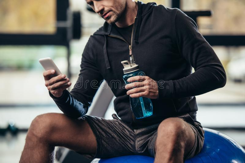 Cropped image of sportsman sitting on fitness ball and using smartphone. In gym stock images