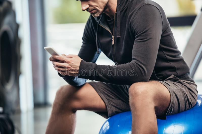 Cropped image of sportsman sitting on fitness ball and using smartphone. In gym royalty free stock images