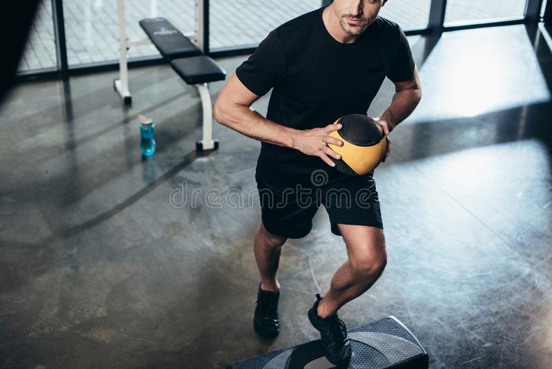 Cropped image of sportsman training on step platform with medicine ball. In gym royalty free stock image