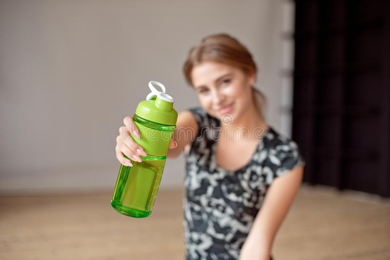 Cropped image of sporty woman holding bottle of water. Cropped image of sporty woman holding bottle of water royalty free stock image