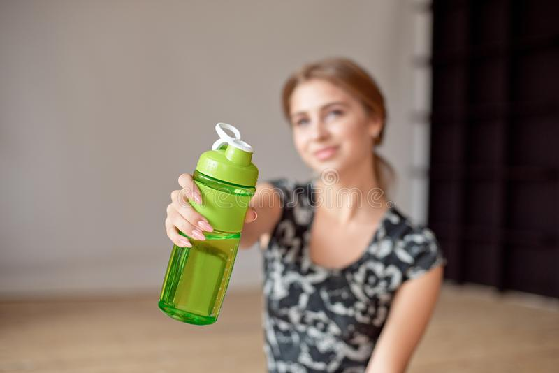 Cropped image of sporty woman holding bottle of water. Cropped image of sporty woman holding bottle of water royalty free stock photo