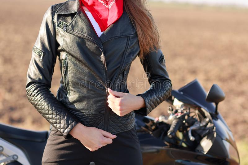 Cropped image of sporty woman zips her black leather jacket, prepares for racing competiotns or marathon, poses near motorbike,. Enjoys extreme sport. People royalty free stock photos