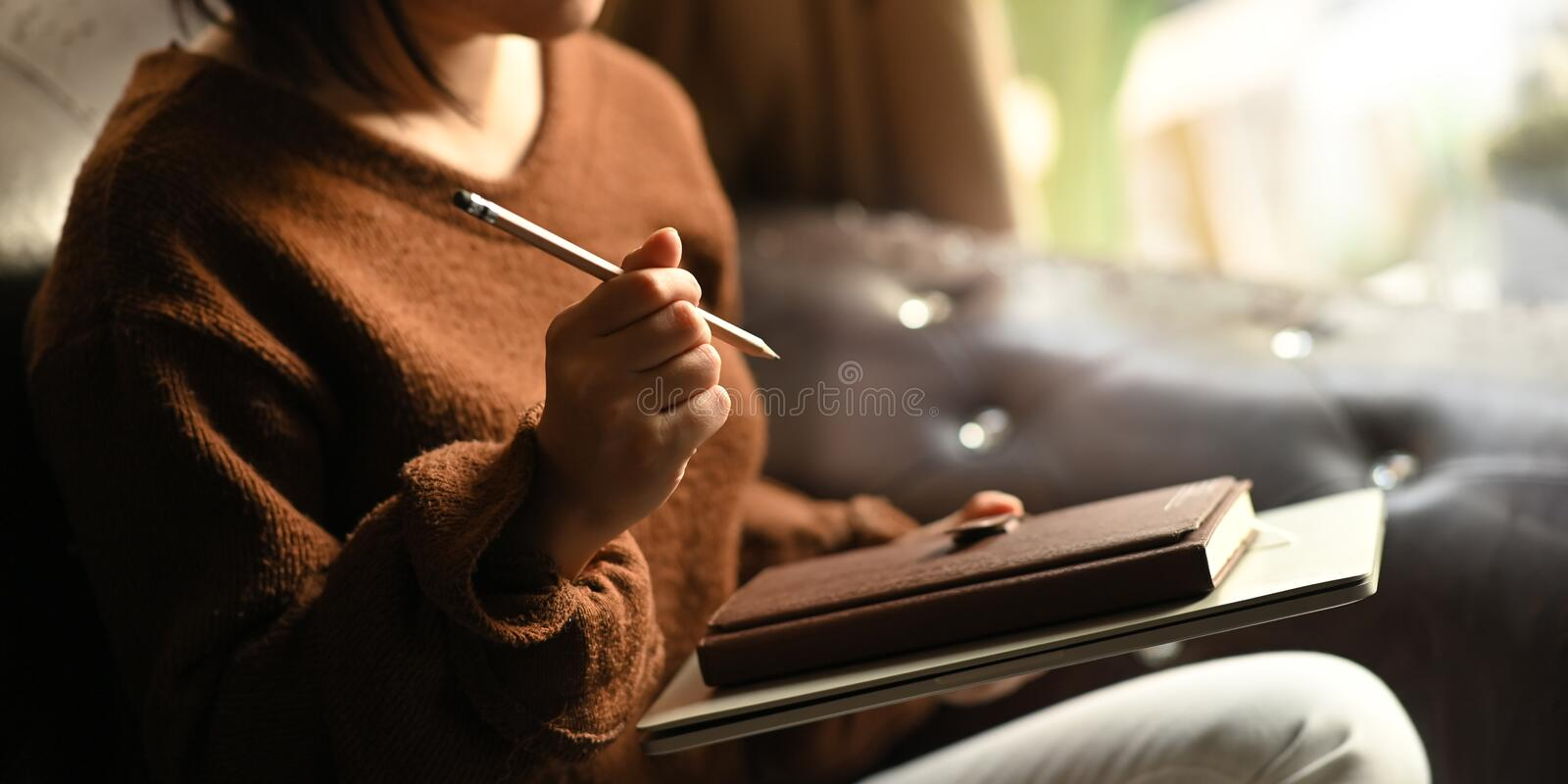 Cropped image of stylish woman holding a pencil and notebook in her hands. royalty free stock photos