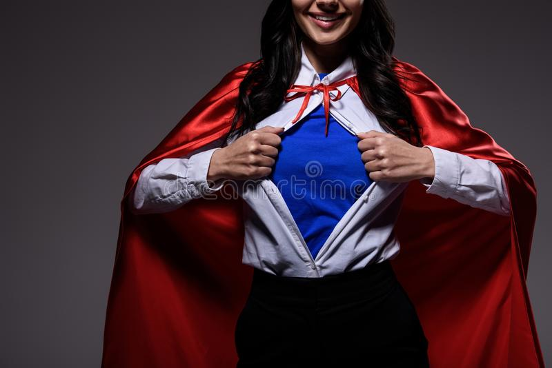 cropped image of super businesswoman in red cape showing blue shirt stock images
