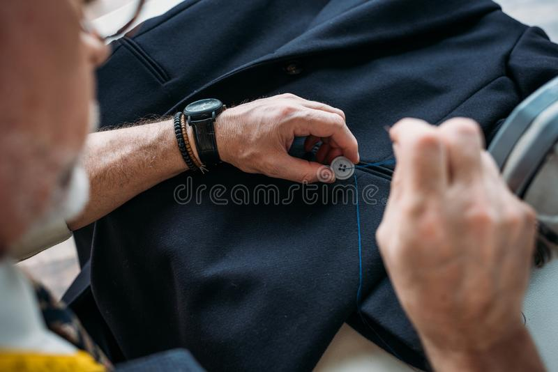 Cropped image of tailor sewing button to jacket. At sewing workshop stock image