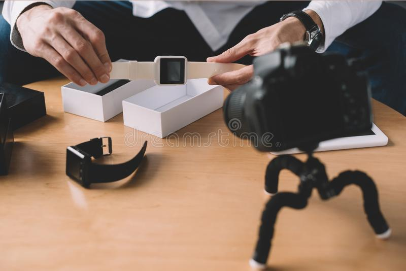 cropped image of technology blogger holding new smart watch in front stock photo
