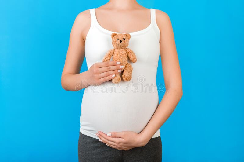 Cropped image of teddy bear in hand against pregnant woman`s belly in home clothing at blue background. Waiting for a childbirth. Copy space royalty free stock photography