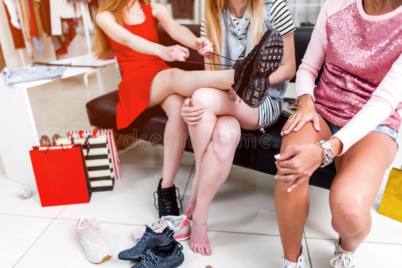 Cropped image of teen girls sitting on bench relaxing after shopping in clothing store. Young stylish woman tying up new royalty free stock image