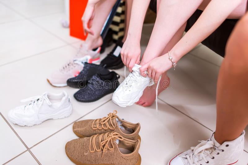 Cropped image of teenage girls trying on sports shoes in a shop stock images