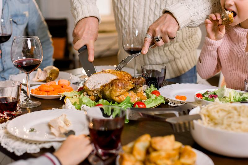 Cropped image of Thanksgiving festive table: Hands of elderly Man Carving Slices Of Roast Turkey For Dinner stock image
