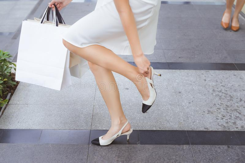 Cropped image of a tired female shopper and shopping bags.  stock image