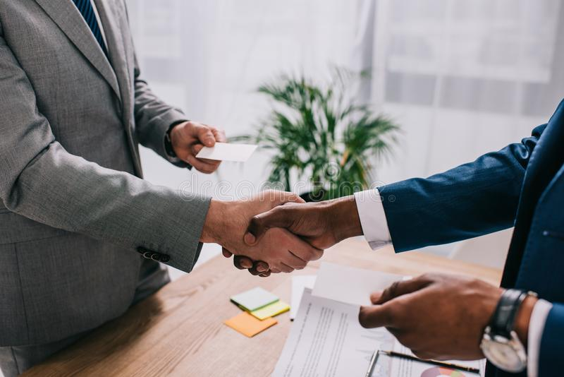 Cropped image of two businessmen shaking hands and giving visit cards to royalty free stock image