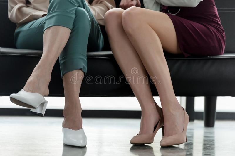Cropped image of two businesswomen sitting on sofa. In office stock photos