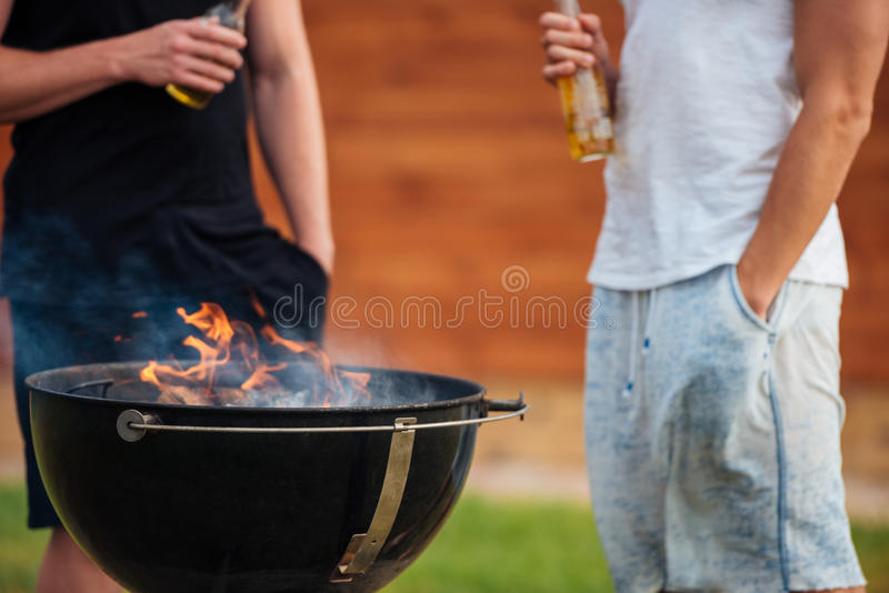 Cropped image of two men holding beer bottles while barbecue. Cropped image of two men holding a beer bottle while preparing barbecue grill in park zone stock image