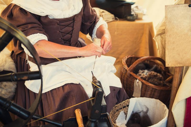 Cropped image of weaver in Middle Agesl clothes make yarn on spinning wheel. Medieval crafts, occupation. The concept of historica. L development of weaving in royalty free stock photography