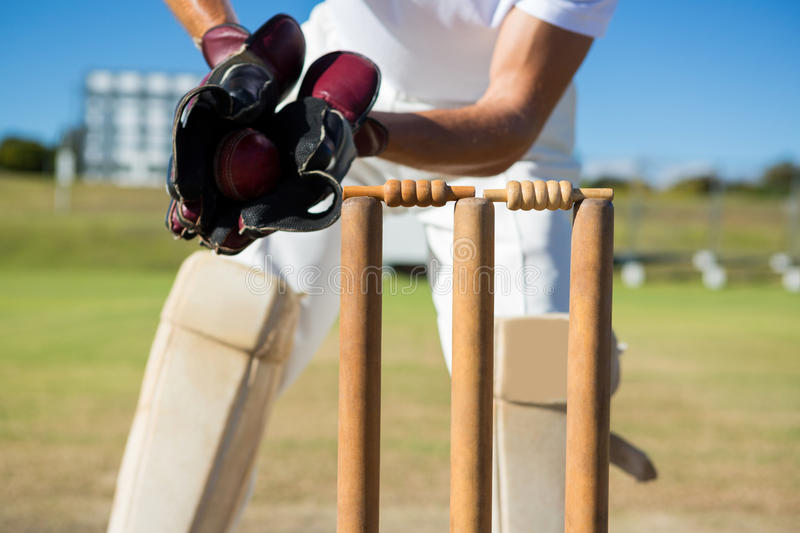 Cropped image of wicket keeper standing by stumps stock photography