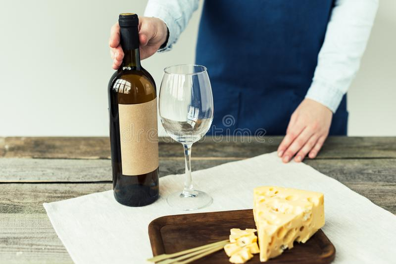 Cropped image of Woman in apron holding bottle of. White wine royalty free stock photos