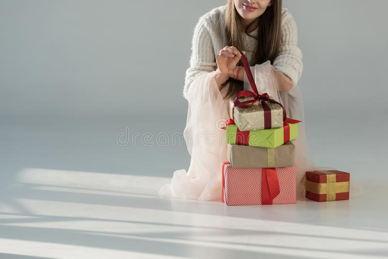 Cropped image of woman in fashionable winter outfit squatting near gift boxes and opening present. On white stock image