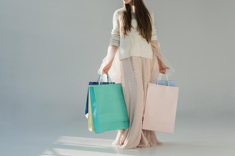 cropped image of woman in fashionable winter outfit standing with shopping bags royalty free stock photo