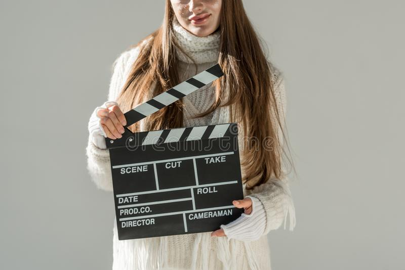 Cropped image of woman in fashionable winter sweater and scarf holding clapper board isolated. On grey stock image