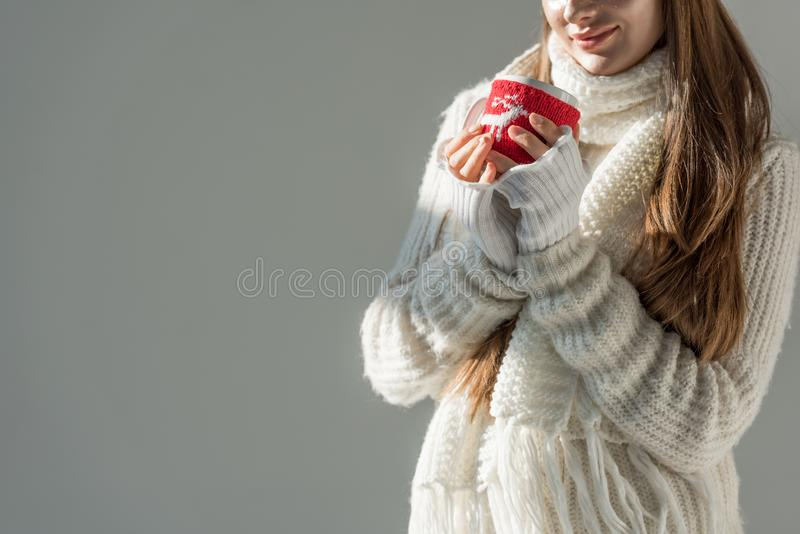 Cropped image of woman in fashionable winter sweater and scarf holding cup of tea isolated. On grey royalty free stock photography