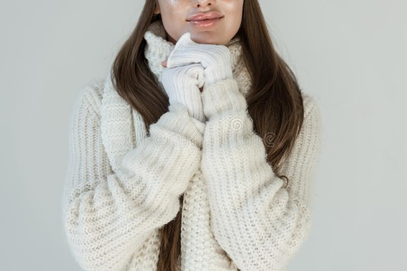 Cropped image of woman in fashionable winter sweater and scarf isolated. On white royalty free stock photo