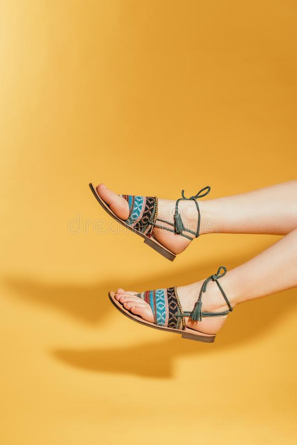Cropped image of woman feet in stylish sandals. On yellow background stock images