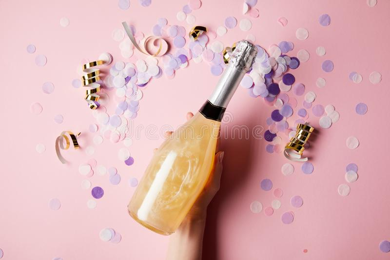 Cropped image of woman holding bottle of champagne above confetti on surface royalty free stock photos