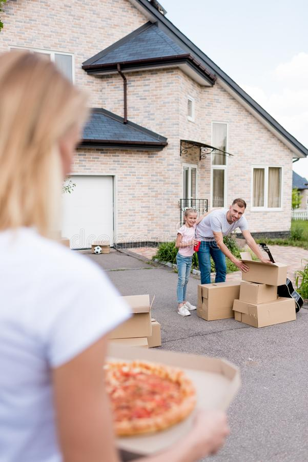 cropped image of woman holding pizza while her husband and daughter unpacking cardboard boxes in front of new stock image