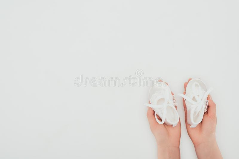 Cropped image of woman holding white baby shoes stock photography