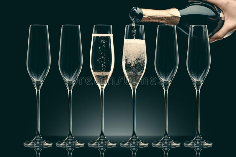 Cropped image of woman pouring champagne from bottle into six transparent glasses stock photography